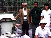 Takejiro Higa at grave of classmate he interrogated in Okinawa during the war