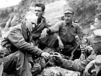 Ernie Pyle, famed war correspondent, shares a smoke with a Marine patrol