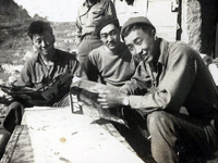 "Atsushi Iwai, Clarence Watanabe, nicknamed ""Big Boy."" and Moriso Teraoka, nicknamed ""Legs,"" relaxing after being on duty in the Maritime Alps. Champagne Campaign. France. Winter of 1944 to Spring of 1945."